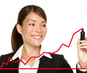 Photo of a female executive creating a line graph that shows an increase in business.